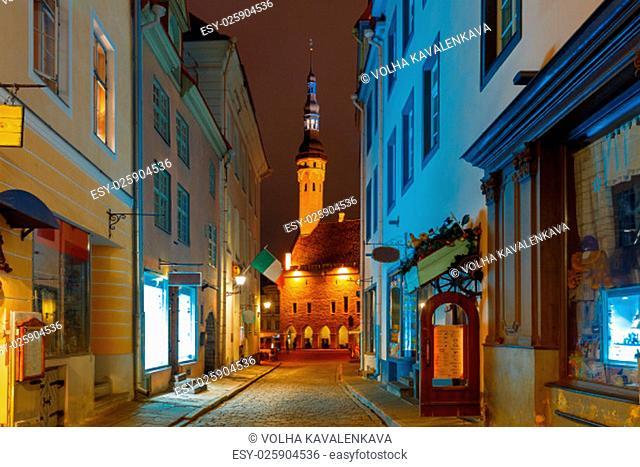 Narrow street illuminated of Old Town at night, City Hall on the background, Tallinn, Estonia