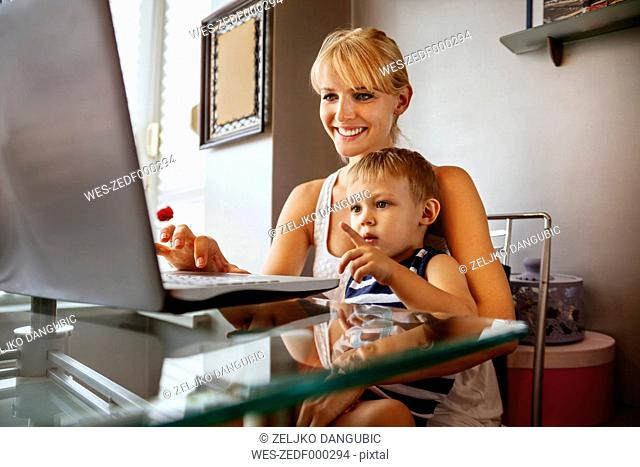 Pregnant woman with sun using laptop