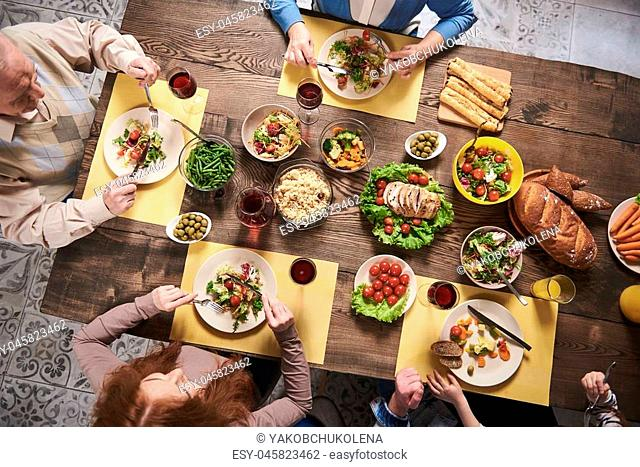 Top view of festive wholesome dishes lying on table. Household members are eating vegetables, salads, meat, bread, rice and drinking red wine