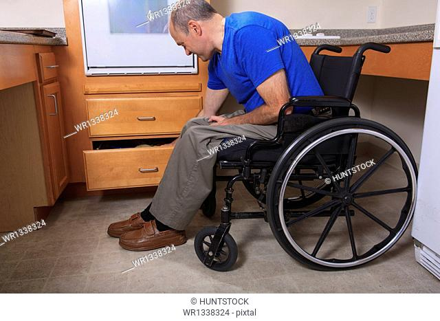 Man with Friedreich's Ataxia and deformed hands accessing items in a kitchen drawer