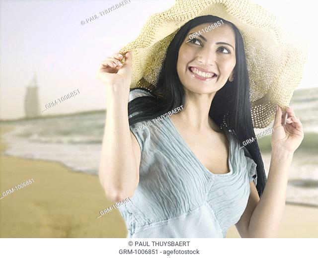 Woman wearing a sunhat on the beach in Dubai (with Burj Al Arab hotel in background)