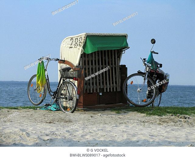 bicycles next to a beach chair at the North Sea, Germany, Lower Saxony, Dornumersiel, Dornum