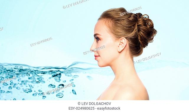health, people, plastic surgery and beauty concept - beautiful young woman face over blue background with water splash