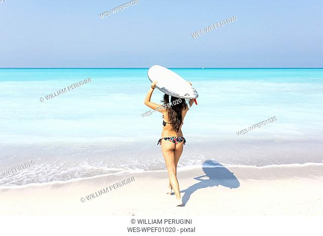 Young woman carrying surfboard to the sea