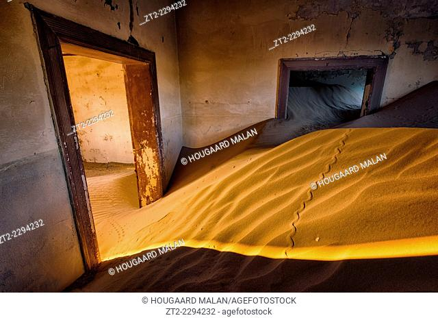 Photo of the interior of one of the old sand-filled buildings at the Kolmanskop mining Ghost Town. Kolmanskop, Luderitz, Namibia