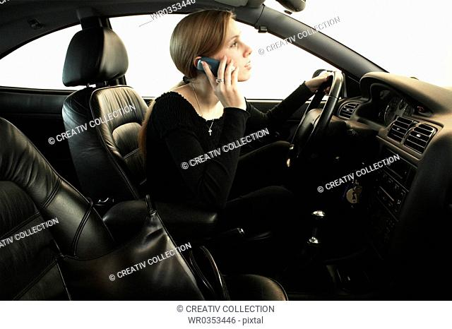 Woman in drivers seat talking on the phone