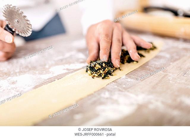 Chef putting ravioli stuffing on dough