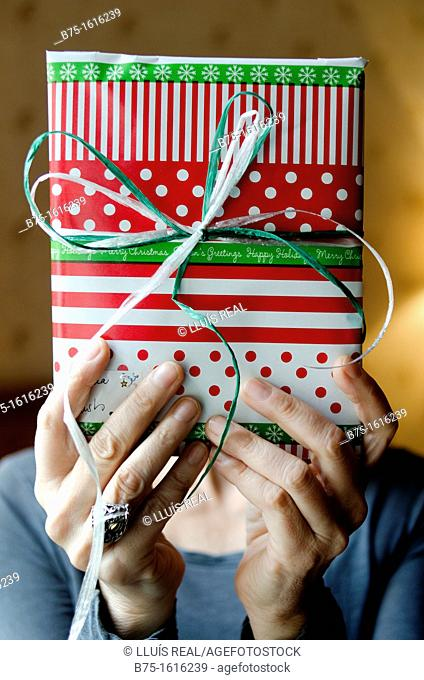Christmas Present in the hands covering the face