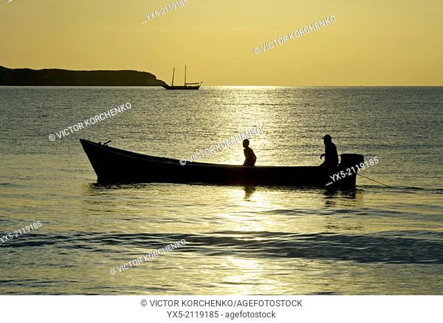 Fishing boat in the open sea at sunrise