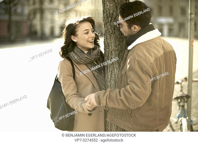 young teenage couple holding hands outdoors around tree in city, in Cottbus, Brandenburg, Germany