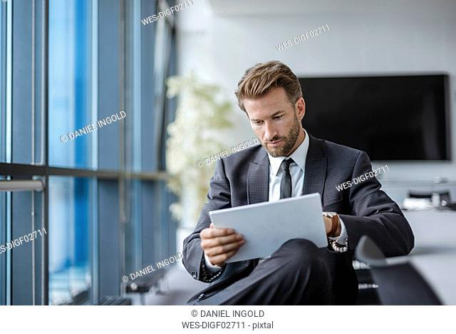 Businessman sitting in conference room using tablet