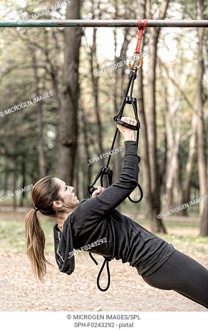 Woman exercising with hanging fitness straps