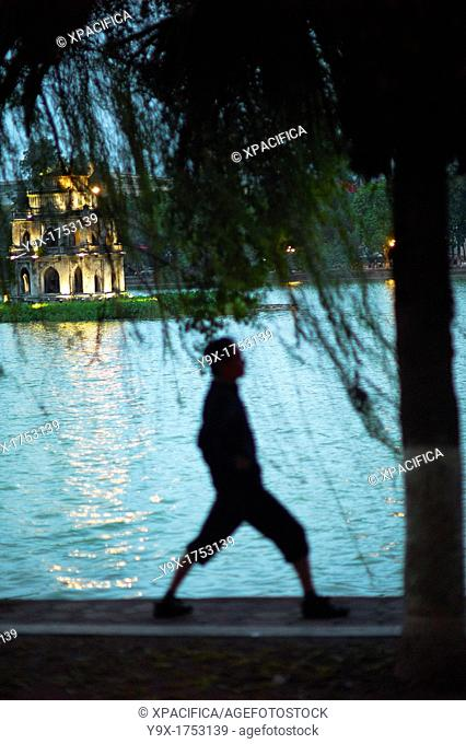 A person doing exercises by the Hoam Kiem Lake in Vietnam