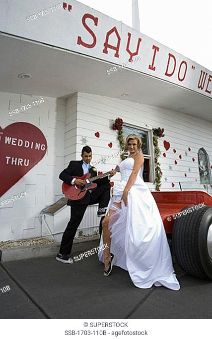 Bride and groom standing beside a drive-thru wedding chapel
