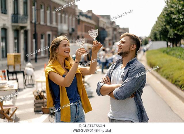 Belgium, Tongeren, happy young couple with glasses on an antique flea market
