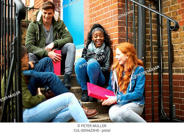 Young adult college student friends chatting on campus stairs