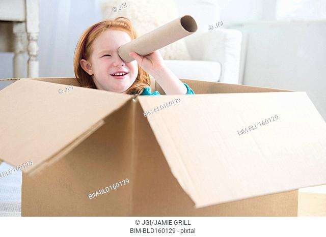 Caucasian girl playing in cardboard box