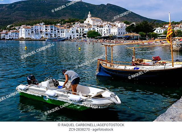 Woman in Inflatable boat next to traditional sailing boats called ''llagut'' moored in front of white village of Cadaqués