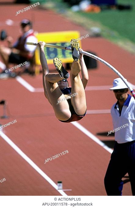 Female pole vaulter bends bar as she attempts a clearance watched closely by judge at track