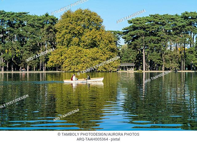 Distant view of three people in rowboat on Lac Inferieur, Paris, France