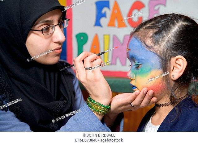 Teacher painting the face of a pupil at the Nottingham Islamia school Aid Fair