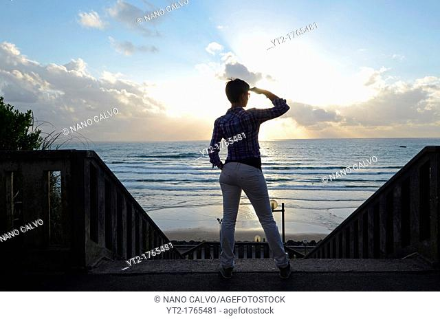 Young woman at sunset in Cote des Basques, Biarritz