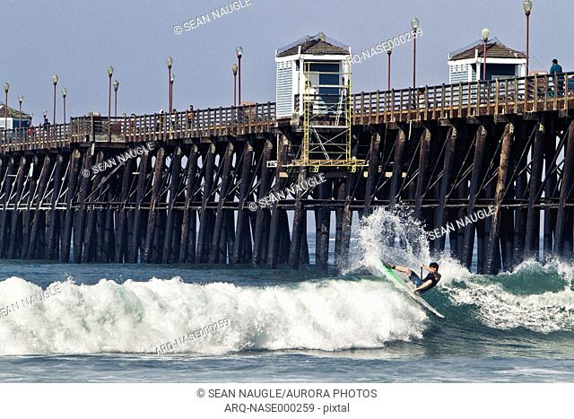 Stand up paddleboarder riding wave near Oceanside Pier, Oceanside, California, USA