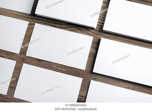 Blank white business cards on wooden background. Mockup for branding identity. Template for graphic designers portfolios