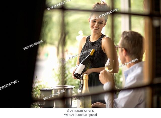 Waitress showing wine bottle to man in restaurant