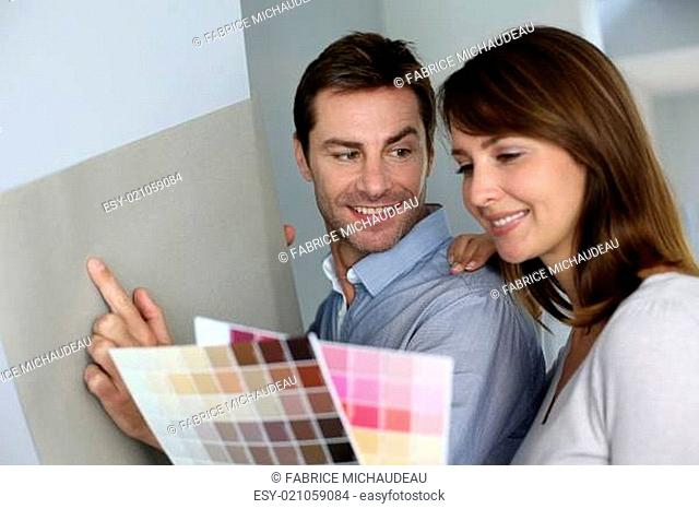 Couple choosing paperwall colour for their new home