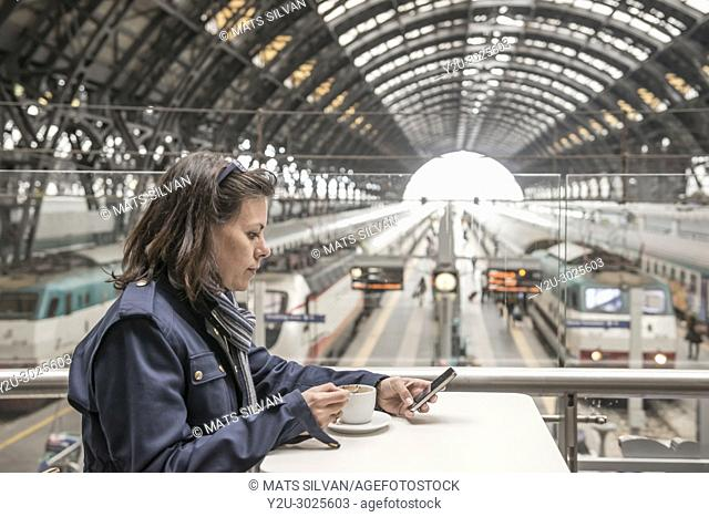 Woman Sitting in a Bar with a Cup of Coffee and Using a Smart Phone in a Train Station in Milan and Waiting in Lombardy, Italy