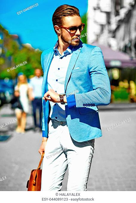 High fashion look.Young stylish confident happy handsome businessman model in suit clothes walking in the street in sunglasses