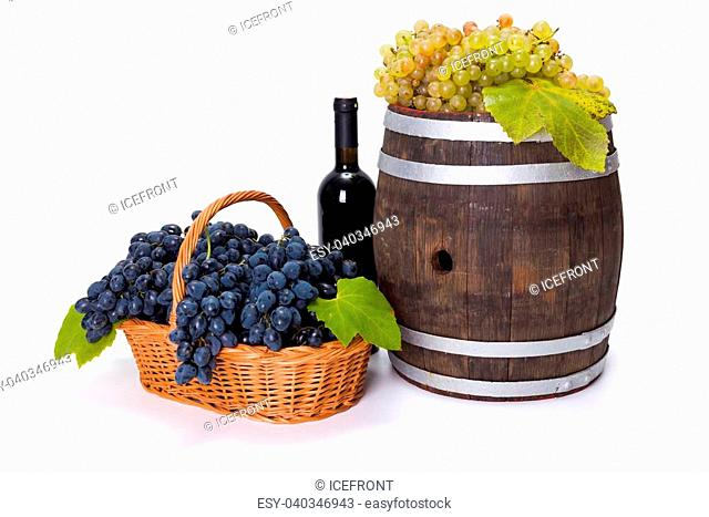 White and white grape in basket with red wine and barrel