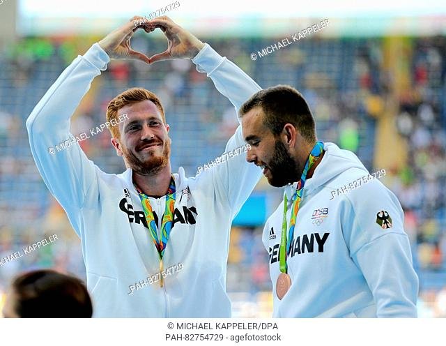 Gold medalist Christoph Harting (L) of Germany and Bronze medalist Daniel Jasinski of Germany celebrate during the medal ceremony after winning the Men's Discus...