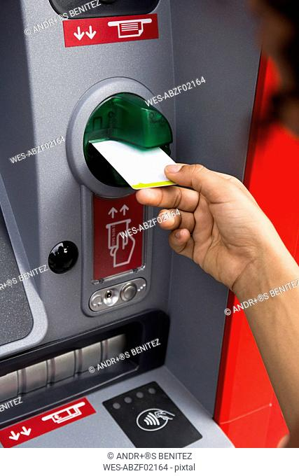 Hand of woman pushing credit card at cash dispenser, close-up