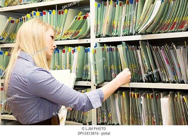 Young woman filing documents at an accounting office; Edmonton, Alberta, Canada