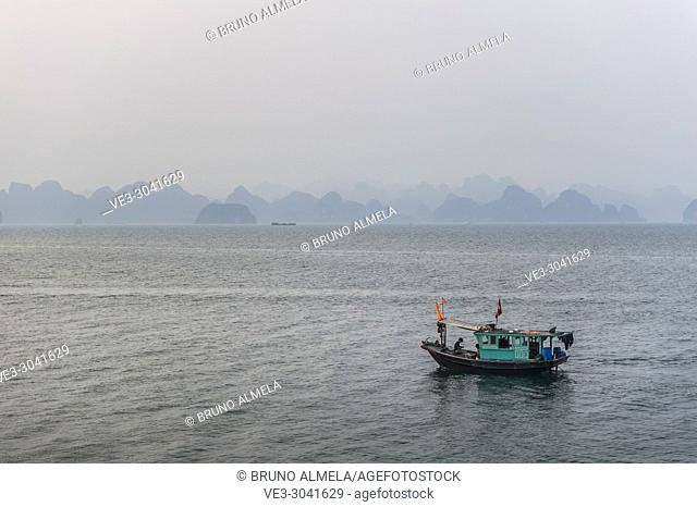 Fishing boat in the karst landscape of Ha Long Bay, Quang Ninh Province, Vietnam. Ha Long Bay is a UNESCO World Heritage Site