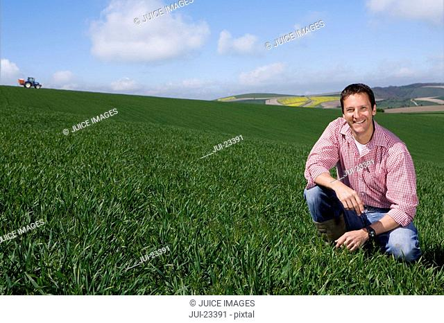 Smiling farmer crouching in sunny, young wheat field