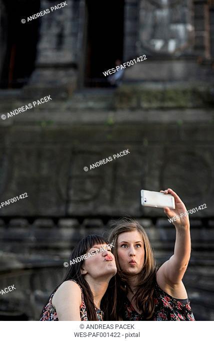 Germany, Koblenz, Deutsches Eck, playful tourists taking selfie at Emperor-Wilhelm monument
