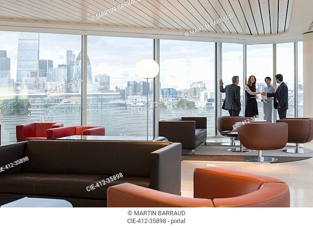 Business people meeting at windows in urban highrise lounge