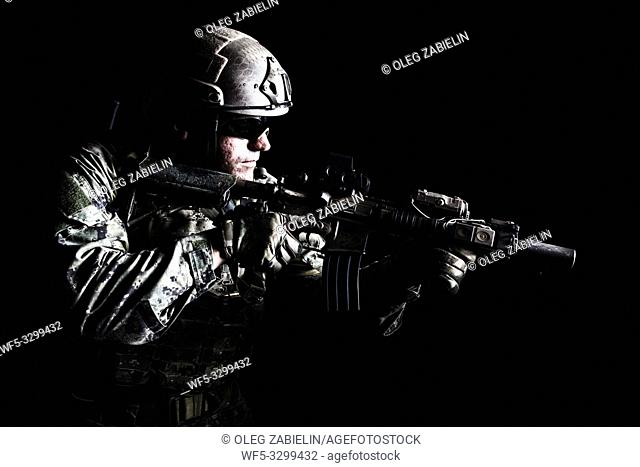 Half length low angle studio shot of special forces soldier in field uniforms with weapons, portrait on black background