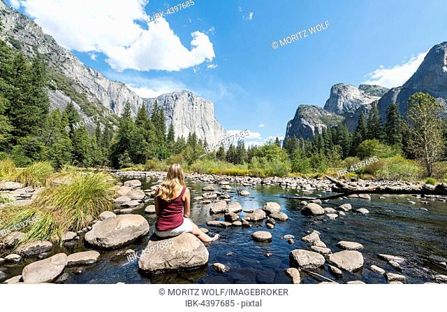Young woman sitting on stone in River Merced, Valley View, view of El Capitan, Yosemite National Park, California, USA