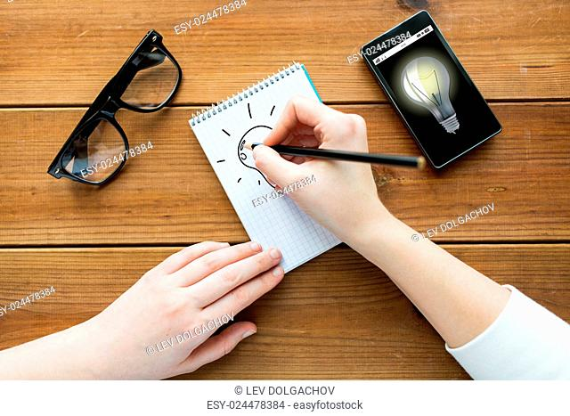 education, business, idea and people concept - close up of woman or student drawing scheme in notepad with pencil and eyeglasses with smartphone on wooden table