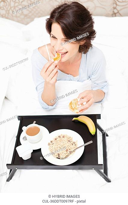 Smiling woman having breakfast in bed