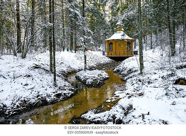 Winter landscape with small river near alcove in a forest