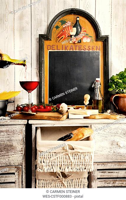 Italian Food, sideboard with typical ingredients, spaghetti, tomato, red wine