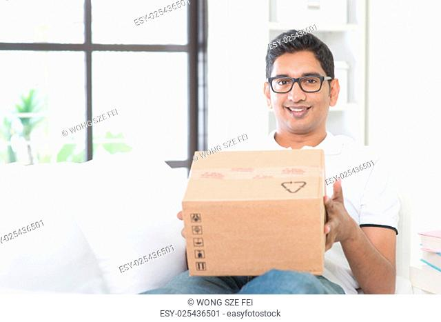 Courier delivery concept. Indian guy received an express parcel and checking the box at home. Asian man sitting on sofa indoor