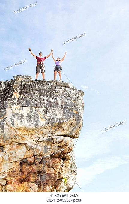 Climbers cheering on rocky cliff