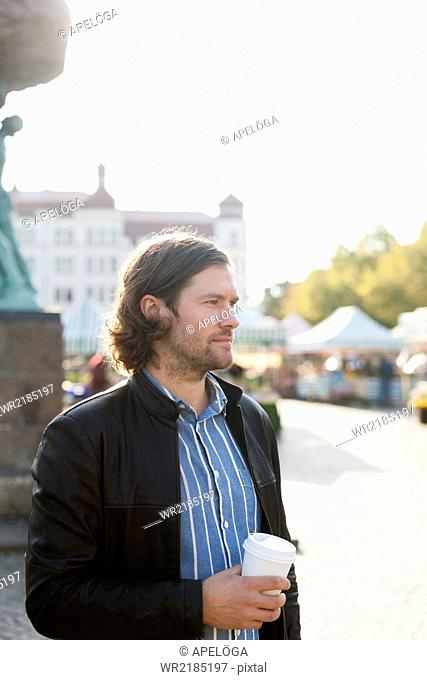 Thoughtful businessman holding disposable coffee cup while standing at marketplace
