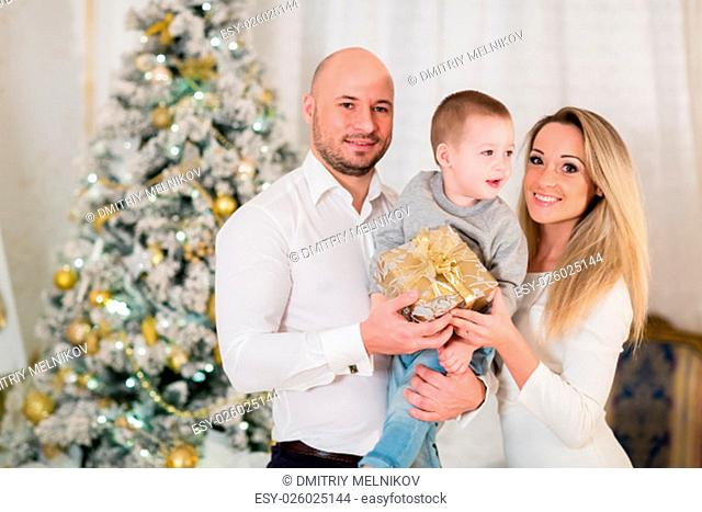 Happy family with gift box stand near Christmas tree in the room. Merry Christmas and Happy New Year